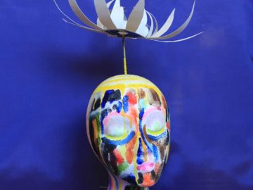 Colorful painted portrait sculpture with paper petaled flower floating above head